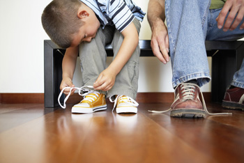 Little Boy Lacing his Shoes